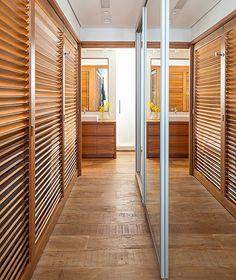Os painéis de freijó dividem o ambiente – quarto de um lado, closet do outro. Os armários com espelhos nas portas ampliam o espaço. Projeto do escritório de arquitetura Archeufficio.