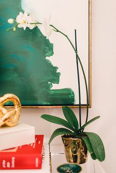 Chic entry vignette with CB2 Peekaboo Clear Console Table topped with stacked books, gold knot and shiny gold planter filled with a white orchid in front of emerald green abstract art in a gold floating frame.