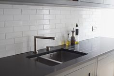 Oak shaker style cabinets painted in Farrow & Ball Down Pipe. Premium black honed granite worktop with built in Stereo STD65 sink. White metro tiles combine perfectly with granite to provide clean lines and simplicity. The contrast of colours make this small apartment kitchen look bigger.