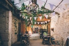 A country courtyard decorated with bunting, horse carts & wheels & hydrangea flowers - Image By Blondie Photography - Bespoke Lace Wedding Dress, Mis-match Pastel Bridesmaids & Navy Groomsmen for a school themed reception & rustic festival after party wedding in Devon.
