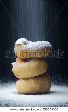 Stack of Donuts sprinkled with sugar over dark background