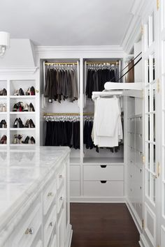 Amazing closet features a long closet island fitted with drawers for accessories topped with marble countertop.