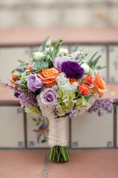 Triadic Orange, lavender, purple, and green bridal bouquet. Purple, lavender, and green are excellent complimentary colors with orange and peach.