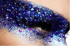 Intense blue eye makeup with tons of glitter and embellishments.
