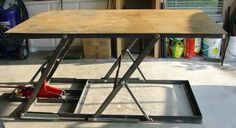 """Lifting Welding Table made with four equal-length 1""""x2"""" tubing risers each pinned to a lower and upper 2""""x2"""" angle frame that are made to nest together to allow the table to fold down to only five inches when fully collapsed. The table is forty-two inches tall when jacked to its full travel."""