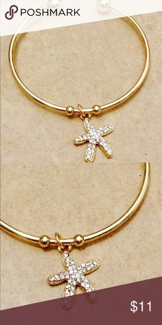 Gold Tone Crystal Starfish Charm Cuff Bracelet Gold tone round open cuff style bracelet features a single charm at the center.  A nautical style starfish with clear crystals.  Open cuff design is a one size fits most.  Starfish charm measures 3/4 inch long x 5/8 inch wide. Jewelry Bracelets