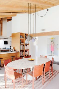Modern, minimalistic dining space with exposed ceiling beams and cartoon artwork
