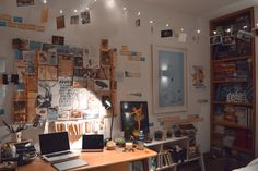 fairy lights mid ceiling hanging in throughout the room and pictures scattered above the light brown desk