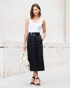 Maria Dueñas Jacobs, Accessories Director for Elle makes a tank top work appropriate by pairing it with a midi skirt and strappy sandals