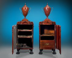 """Regency-period dining pedestal cupboards by English furniture designer, George Smith. One mahogany pedestal serves as dish warmer and features a lead-lined interior with two slatted shelves and a cast iron grill in the base. The other serves as wine cellarette and contains shelving and a drawer for  liqeurs. The stepped pedimented tops give way to reeded, hinged doors. Ebonized lion feet complete the design. On each pedestal are mahogany cutlery urns.  23"""" wide x 20"""" deep x 68"""" high Circa…"""