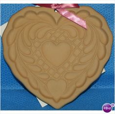 """Quilted Heart - Brown Bag Cookie Mould - An American Collectible    Brown Bag Cookie Moulds have become an American classic - collected, loved and used to make very special cookies, chocolates and innumerable crafts. The ceramic mould is about 6"""" across and dishwasher safe.    In 2006, Brown Bag Cookie Art announced the retirement and discontinuation of its ever-popular cookie moulds."""