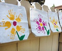 "Love these store bought totes emblazoned with the ""flower hands"" of those you love. Just use cheap acrylic paints with a little dab of textile medium mixed in (available at your craft store.) Yes, cupcake, you an also get inexpensive fabric paint if you're the anal type! LOL Freehand the stem and leaves!"