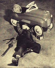 a child performs auto repair on his pedal car 1950