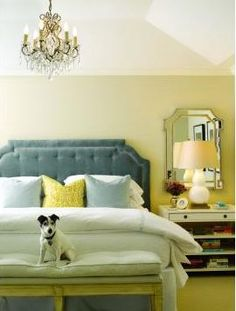 Bedroom with blue upholstered headboard, taupe walls, a crystal chandelier, a white nightstand, an arched vintage inspired mirror and an upholstered bench at the foot of the bed with a jack russell terrier sitting on it.