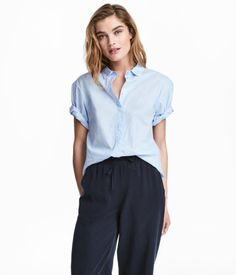 Light blue. Straight-cut shirt in airy, woven cotton fabric with a collar. Concealed buttons at front, dropped shoulders, and short sleeves with sewn cuffs.