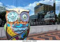 An Owl figure on the Big Hoot Trail in Birmingham. The Library of Birmingham is clearly reflected in glass behind - Stock Image