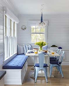 An all-white breakfast nook, accented with shades of blue, is an inviting place to dine with friends and family. An L-shaped, built-in banquette and four cushioned, metal chairs offer casual and comfortable seating.