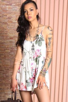 Charmingly feminine floral romper by Somedays Lovin featuring oversized drapey fit in an all-over floral print complete with a buttoned placket, scoop-neck, side pockets and thin adjustable straps.