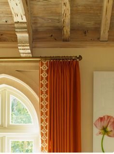 rough hewn, natural ceiling beams and sophisticated burnt orange linen drapery  .  a comfortable combination