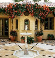 Palm Beach Romance    A 15th-century Moroccan fountain sits in a dramatic apron of simulated coquina outlined with black Mexican river stones. Orange bougainvillea dresses the bay window.