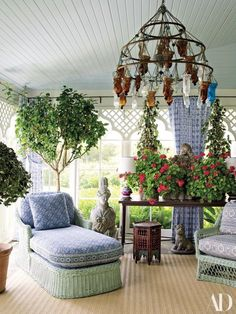 Moorish arches frame the windows of the plant-filled sunroom at Woody house. Vintage wicker furniture features cushions of custom Peter Marino fabrics. Three-tiered Moroccan chandelier.