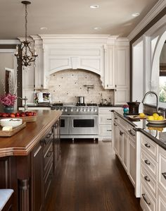 A traditional styled kitchen remodel with white cabinets from Dura Supreme Cabinetry, a dark stained kitchen island and a grand wood hood over a large double oven and stove top. Double Oven Kitchen, Kitchen Oven, Kitchen Hoods, New Kitchen, Kitchen Decor, Kitchen Island, Kitchen Ideas, Kitchens With Double Ovens, Kitchen Designs