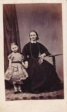 1860s girl and mother. Quite a decorative hem and pockets.