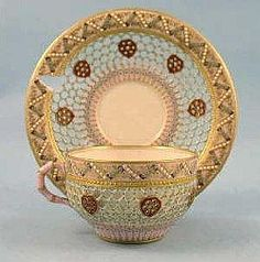 Royal Worcester reticulated porcelain cabinet cup and saucer, each piece with turquoise and gilt dotted pierced trellis band within a white and turquoise jewelled ribbon pink grounded border, the double- walled cup applied with a faux bamboo handle, section of border to saucer lacking, the cup with green printed mark and date code for 1878 the saucer with green printed mark and date code for 1886