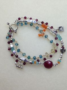 Vibrant colors make this bracelet a must-have! All Sterling Silver beads and charms, wire-wrapped Rhodolite Garnet, Blue Apatite, Ruby and Carnelian faceted gemstones with a couple of Citrine rondelle