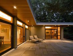 Exterior Modern Boston chaise lounge flat roof glass doors outdoor lighting overhang Patio patio furniture pavers roof line sliding doors soffit TRANSOM wood ceiling Design Exterior, Roof Design, Modern Exterior, House Design, Patio Design, Bungalow Extensions, House Extensions, Roof Overhang, Roof Deck