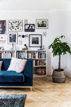 Granatowa sofa i mała biblioteczka w salonie