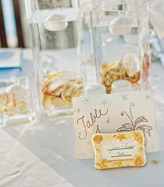 Starfish and seashells with a floating candle make these centerpieces just beachy!