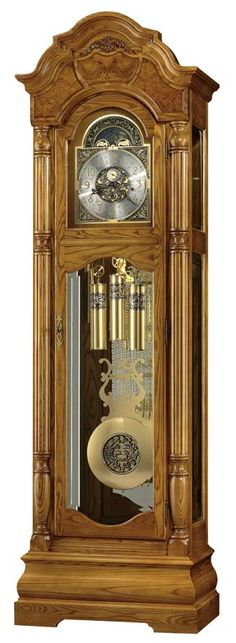 """Howard Miller Scarborough 611-144 Grandfather Clock.     Special 82nd Anniversary Edition floor clock features a distinct bonnet pediment with book-matched olive ash burl overlays and a decorative carved applique.   Brushed satin brass finished dial features cast center and corner ornaments, and a moon arch with an astrological blue moon phase.  Finished in Legacy Oak.  Key-wound, triple chime movement with automatic nighttime chime shut-off option.  Size: H. 88-1/2"""" W. 27"""" D. 16"""""""