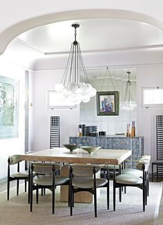 A Spanish-Style 1920s Bungalow Gets a Modern Makeover Photos | Architectural Digest. The dining room's bleached-oak table was chosen to create a more intimate conversational flow during the couple's dinner parties. The bubble chandelier is by Apparatus Studio, and the chairs by Dan Johnson are vintage.