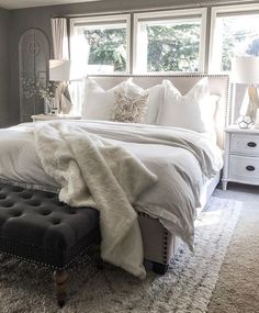 White bedroom with dark seating at the end