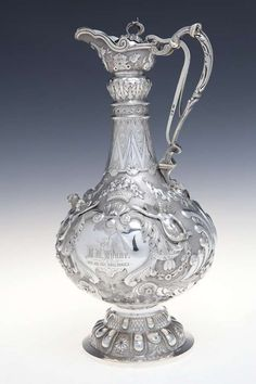 A FINE IRISH VICTORIAN SILVER CLARET JUG/TROPHY CUP, Dublin 1888, by West & Sons, in the form of an Armada jug with long neck and trigger hinged lid with c-scroll handle, presented by The Dublin Rifle Club, Leinster Cup to Edward Nixon Wynne, Wentworth House, Co. Wicklow, for the 800 and 1000 yard ranges, the stippled round decorated with baskets of flowers, geometric banding with cartouches flanked by winged cherubs in relief, griffin heads and woodland masks, raised on a panelled circular…