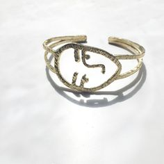 { PRODUCT } -Human face Bangle made from brass . Inspired by my favorite illustrator.  { DIMENSION }  - 7 cm. ( 2.5 inches ) in diameter , adjustable - Face = 2.6 cm. x 4 cm.