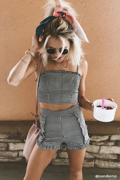 A woven crop top featuring an allover gingham plaid print, adjustable cami straps, a square neckline with ruffle trim, elasticized center back panel with smocked detail, a concealed side seam zipper, and form-fitting silhouette.