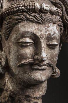 Tête de Boddhisattva à la beauté hellénistique, le visage juvénile, les yeux mi-clos exprimant sa grande compassion, le nez aquilin, les lèvres fines surlignées d'une moustache frisée, les lobes des oreilles allongés par de lourds pendants marque de sa noblesse, l'Urna troisième œil au milieu du front symbole de sa clairvoyance, la chevelure ondulée en longue boucles retenues par un serre tête joyaux. Stuc. Art Gréco Bouddhique du Gandhara. 2ème à 3éme siècle.33cm.