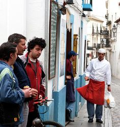 """""""Cook & the Corner Boys"""" - On a narrow, ancient street of old town #Cordoba, #Spain, the corner boys loitering outside a restaurant pique the ire of the in-house chef in a moment of compelling local friction. #streetphotography #fineartamerica"""