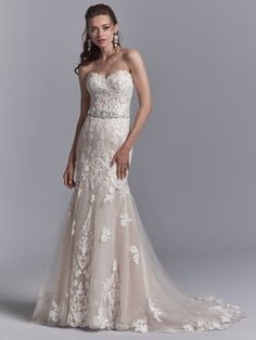 Romantic lace motifs dance over tulle in this fit-and-flare wedding dress, featuring a beaded belt accented in Swarovski crystals, a strapless sweetheart neckline, and illusion scoop back with exposed…