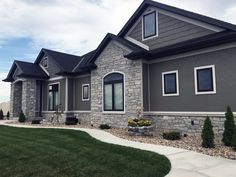 Natural Stone veneer siding isn't exactly new. It's been used as an architectural element for thousands of years. What are the main benefits? Stucco And Stone Exterior, Stucco Homes, Stone Home Exteriors, Home Exterior Makeover, Exterior Remodel, Grey Stone House, Stone Front House, Grey Siding House, Stone Veneer Siding