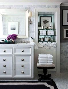 white bathroom with moulding details, mirrored back marble subway, mosaics floor, black rug