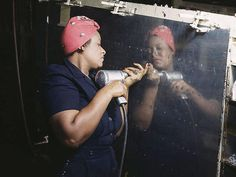 """Feb. 1943   Operating a hand drill at Vultee-Nashville, woman is working on a """"Vengeance"""" dive bomber, Tennessee."""