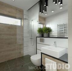 drewnopodobne ceramiczne płytki na ścianie z wąskim oknem wi prysznic ze szklanym panelem ścianką,białe i lustrzane panele na ścianie z umywalką w nowoczesnej łazience