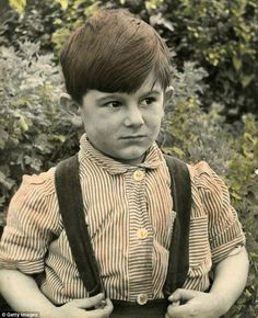 Ronnie Wood, aged four, dressed in a striped shirt and dungarees, is pictured at his home in Whitehorn Avenue, Yiewsley, West London, in 1951