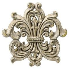 """A lovely addition to your living room or entryway, this eye-catching wall decor showcases a fleur-de-lis design for stylish appeal.       Product: Wall decor   Construction Material: Polyurethane     Color: Aged cream   Features: Fleur-de-lis design    Dimensions: 18.5"""" H x 18.5"""" W x 2"""" D"""