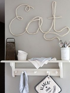 "Create a real statement wall in your kitchen with a cursive request to ""Eat."" Dipping jute rope in a glue-based mixture will make the message stick. Get the tutorial at Love Grows Wild..."