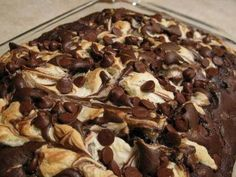 Ingredients:  1 Cup Flaked Coconut  1 Cup chopped Pecans  1 Box German Chocolate Cake Mix  1 (8 oz.) package cream cheese  4 cups confectioners' sugar  ½ cup butter  1 teaspoon vanilla extract  Chocolate Chips          Instructions: