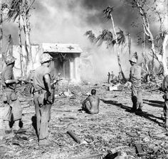 Japanese soldier is surrounded by  Marines of the 4th Marine Division. He is stripped naked to show that he does not have grenades strapped to his body. Still, there are at least three barels on him. Unidentified location, 1945.